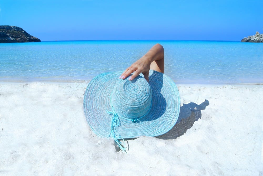 Prevention from sun damage being depicted by wearing a large brimmed hat whilst on the beach in the sun.