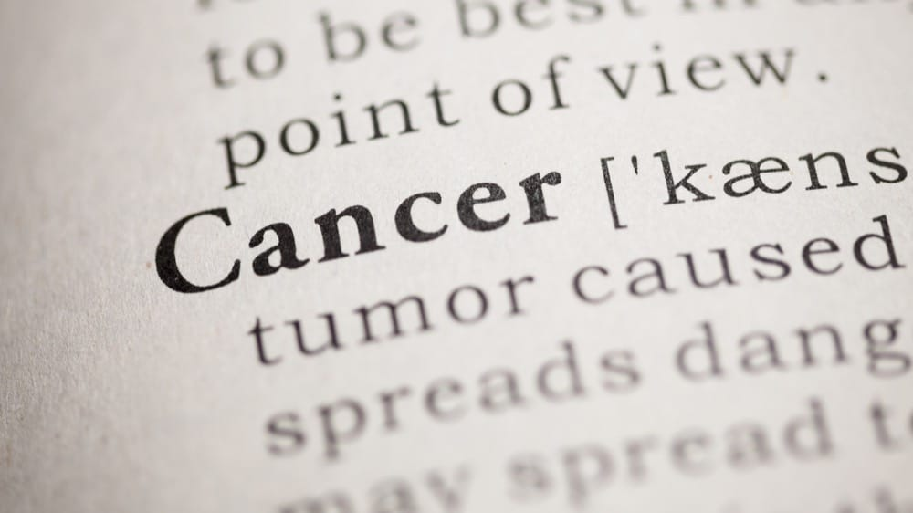 The word Cancer highlighted in bold at the beginning of a page from a dictionary. It is providing the definition of Cancer.